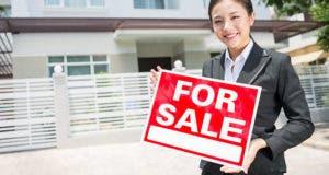 Female broker holding a for sale sign © Dragon Images/Shutterstock.com