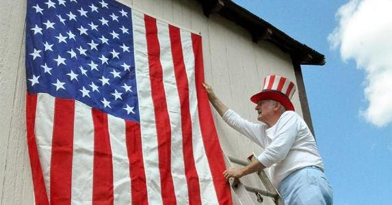 Senior man fixing U.S. flag hanging on wall | Dorann Weber/Getty Images
