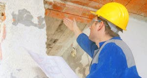 Inspector holding plan checking building © vidguten/Shutterstock.com