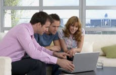 Real estate agent using laptop with couple in new home © bikeriderlondon/Shutterstock.com