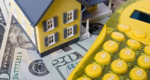 Yellow house and calculator on money © iStock.com