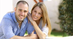 Couple posing outside their home