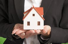 Real estate agent holding house in hands © alphaspirit/Shutterstock.com