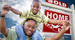 Father and son buying house outside by sale sign © Andy Dean Photography/Shutterstock.com