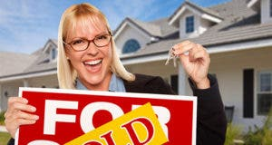 Real estate agent holding 'Sold' sign and keys © Andy Dean Photography/Shutterstock.com