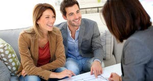 Couple looking at house plans with agent © Goodluz/Shutterstock.com