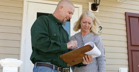 Man reviewing clipboard information with woman