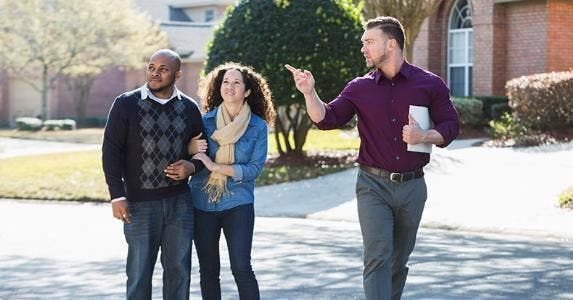 Couple walking around neighborhood with real estate agent | kali9/Getty Images