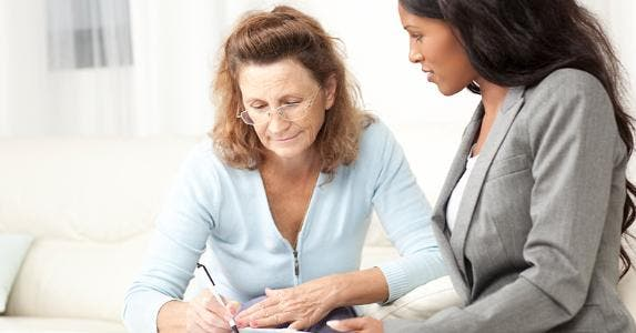 Adviser helping woman sign forms © iStock