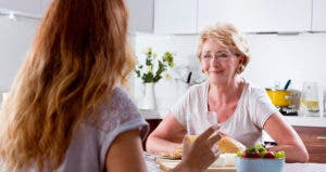 Senior woman listening to female relative in kitchen table © iStock