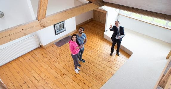 Realtor showing couple an exposed ceiling © iStock