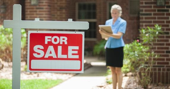 'For sale' sign with agent in background © iStock