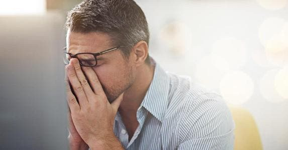 Stressed man holding bridge of nose | iStock.com