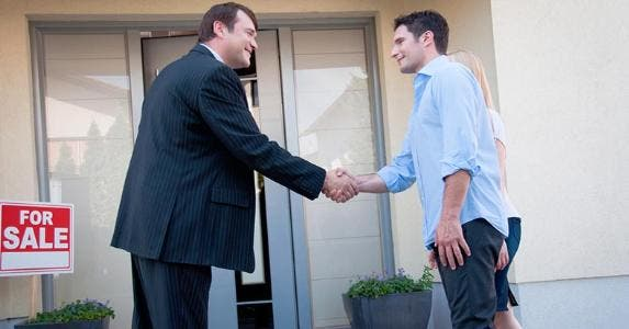 Young homebuyer couple shaking hands with agent | iStock.com/Tashi-Delek