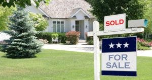 'Sold' and 'For Sale' sign in front lawn of house | iStock.com/Lisa Thornberg