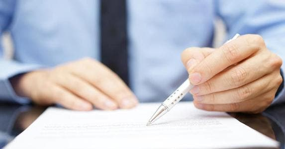 Agent pointing at contract with pen tip © iStock