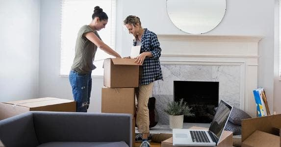 Young couple unpacking boxes in living room | Hero Images/Getty Images