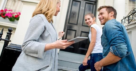 Young couple with real estate agent entering house | iStock.com