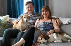 Couple sitting on couch with their 2 dogs | The Washington Post/Getty Images