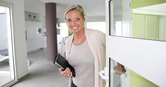 Agent opening door with a smile © goodluz/Shutterstock.com