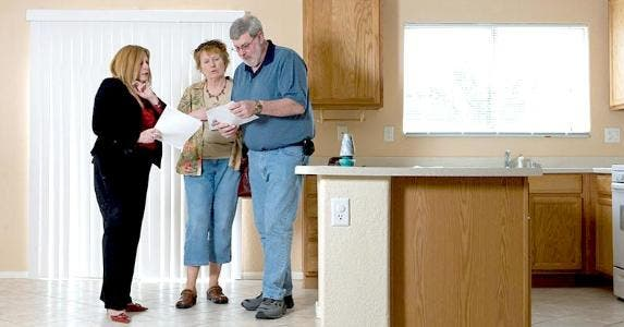 Couple talking with realtor in the kitchen | Jared McMillen/Getty Images