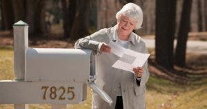 Woman leaning on mailbox, reading mail | Mark Edward Atkinson/Getty Images