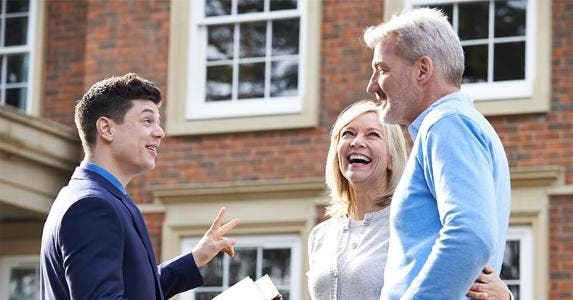 Mature couple talking to real estate agent | SpeedKingz/Shutterstock.com