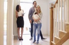 Young couple with infant foyer checking out a house with real estate agent | Monkey Business Images/Shutterstock.com