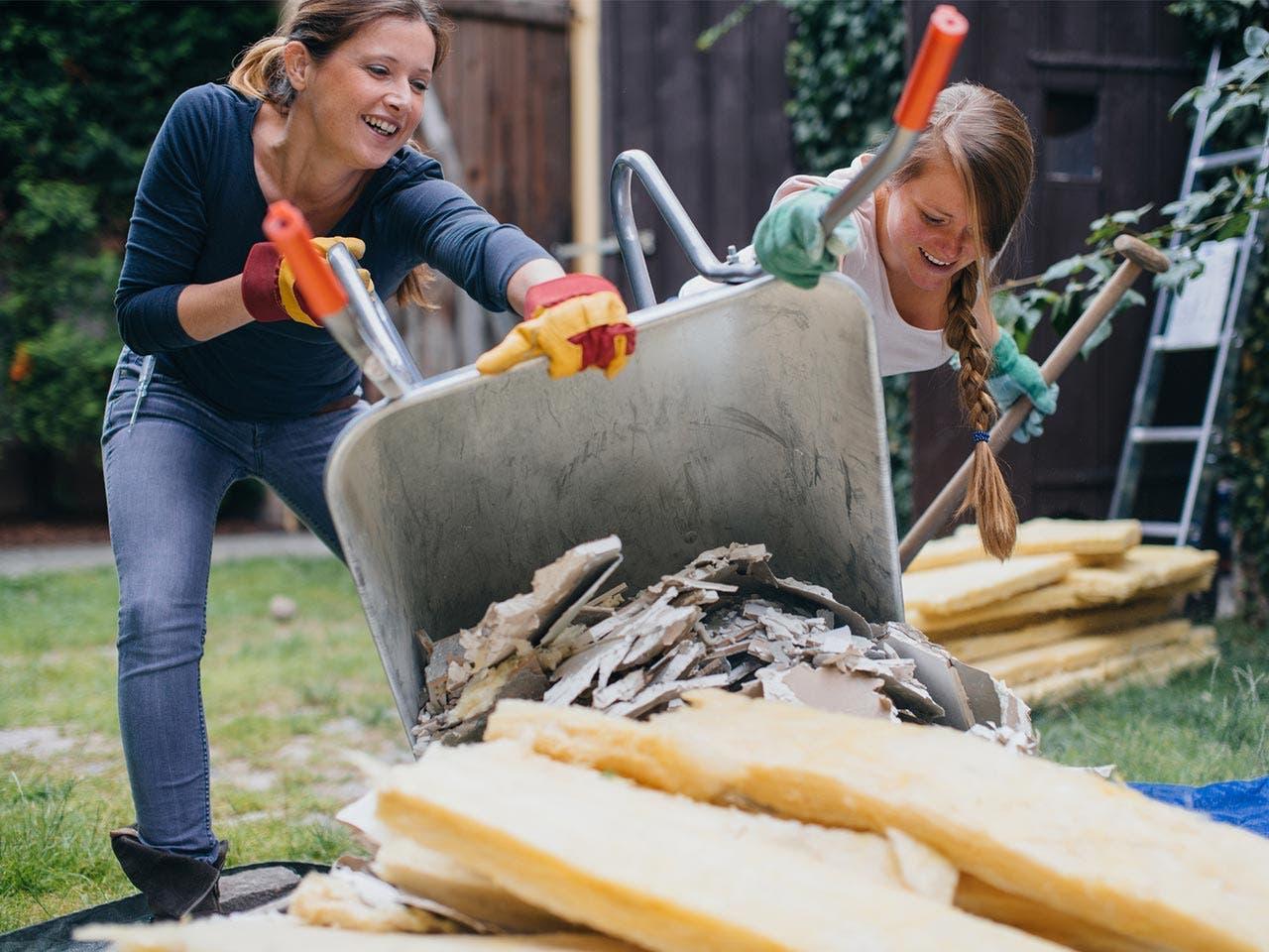 Women pouring garden scrap out of the wheelbarrow