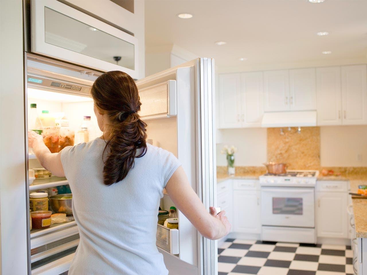 Woman reaching inside her refrigerator