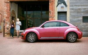 Two women walking towards a red Volkswagen Beetle