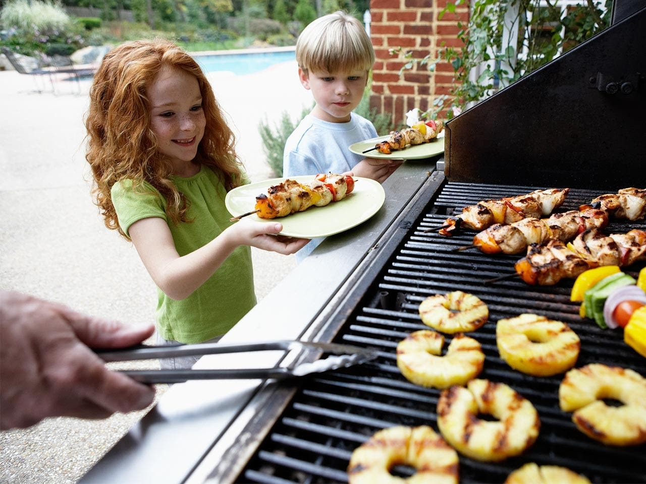 Kids taking food from grill