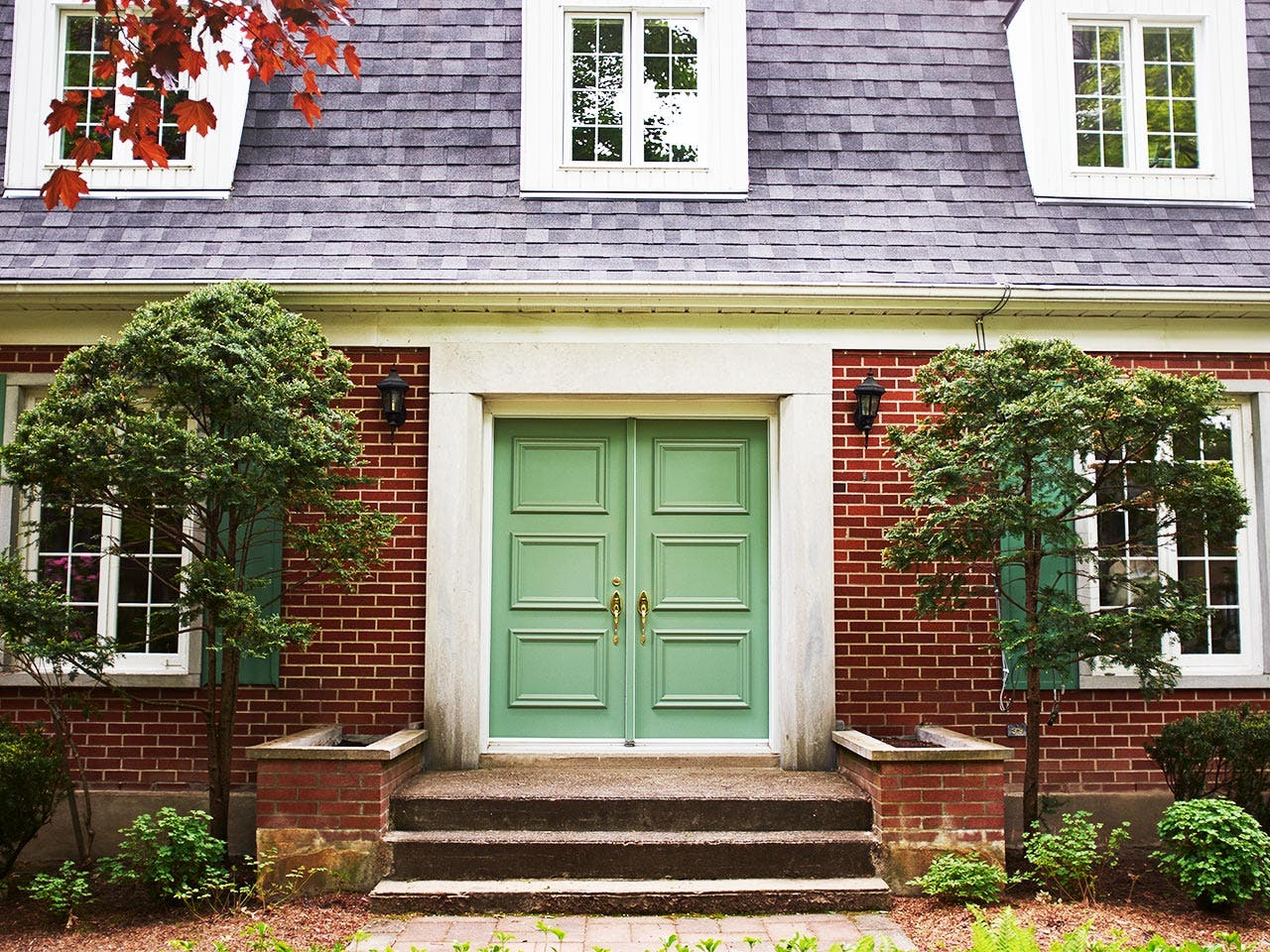 Front of house showing green double doors