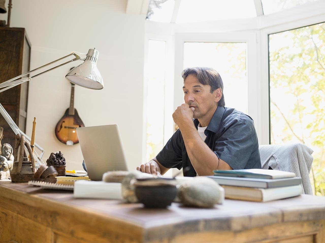 Man thinking, seated at his home desk