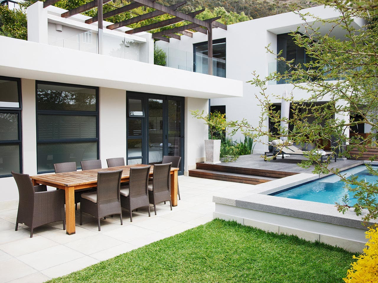 Backyard of house with nice pool and patio table