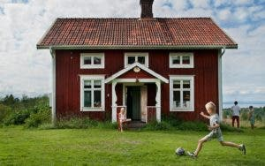 Kids playing in yard in front of red house