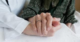 Doctor and elderly woman holding hands © sezer66/Shutterstock.com
