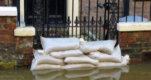Flooded home entrance blocked by sandbags © ronfromyork/Shutterstock.com