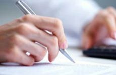 Hand holding pen and using calculator © YanLev/Shutterstock.com