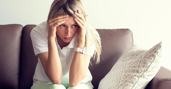 Nervous woman sitting on a couch © iStock