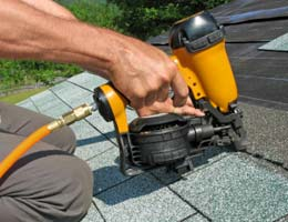 Construction worker stapling new shingles