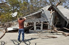 Man looking at destroyed home © John Wollwerth/Shutterstock.com
