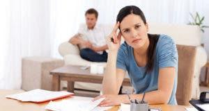 Distressed woman at desk man in background © wavebreakmedia/Shutterstock.com