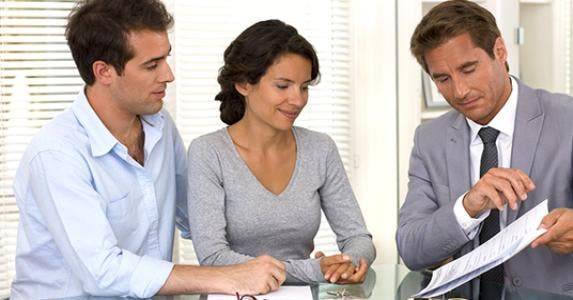 Consultant presents paperwork to young couple © LDprod/Shutterstock.com