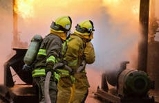 Three firefighters putting out fire © Johnny Habell/Shutterstock.com