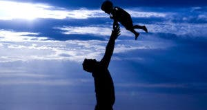 Father tossing son silhouette on a beach © Mehmet Dilsiz/Shutterstock.com