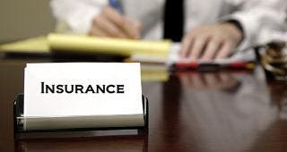 Agent with insurance card on desk © Lane V. Erickson/Shutterstock.com