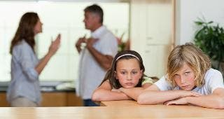 Sad children with parents fighting in background © wavebreakmedia/Shutterstock.com