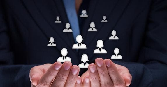 Employee icons floating in cupped hands © Jirsak/Shutterstock.com