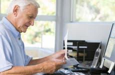 Senior at desk looking over paperwork © Monkey Business Images/Shutterstock.com